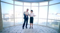 Businessmen man and woman discuss work project in a modern office building near clean panoramic window. Business concept. Steadicam shoot video