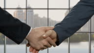 Businessmen shake hands at daytime. video