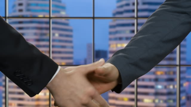 Businessmen shake hands at night time. video