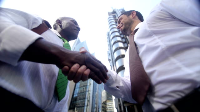 Businessmen shaking hands outside offices video