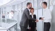 DS Businessmen shaking hands with his collegues on a busy corporate hallway video