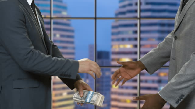 Businessmen with money shaking hands. video