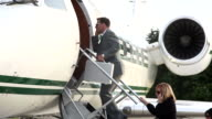 Businesspeople board corporate jet video