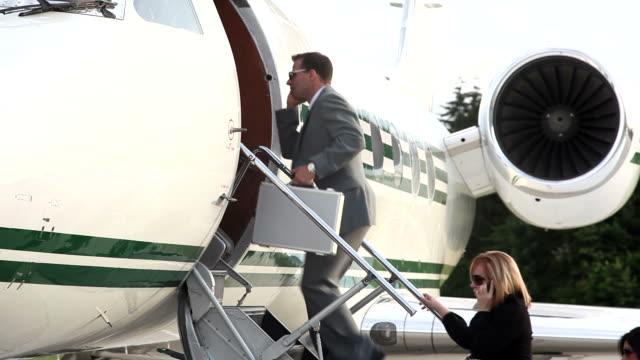 Businesspeople board corporate jet video
