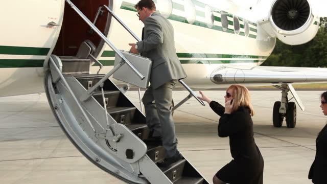 Businesspeople board jet video