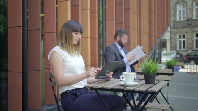 Businesspeople consulting data on tablet during work. Outdoor. Steadycam shot. video