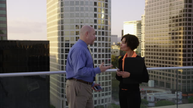 Businesspeople meet on rooftop and shake hands video