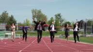 Businesspeople racing across finish line video