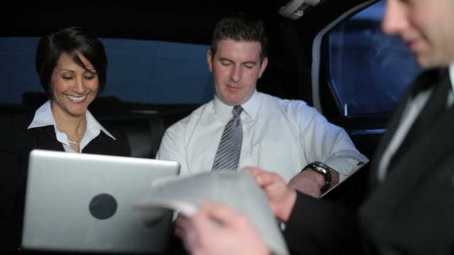 Businesspeople working inside limo video