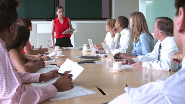 Businesswoman addressing group of colleagues seated around boardroom table.Shot on Sony FS700 at frame rate of 25fps video