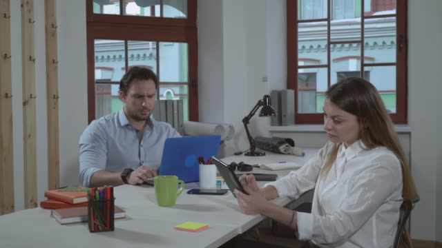 Businesswoman and businessman working in office video