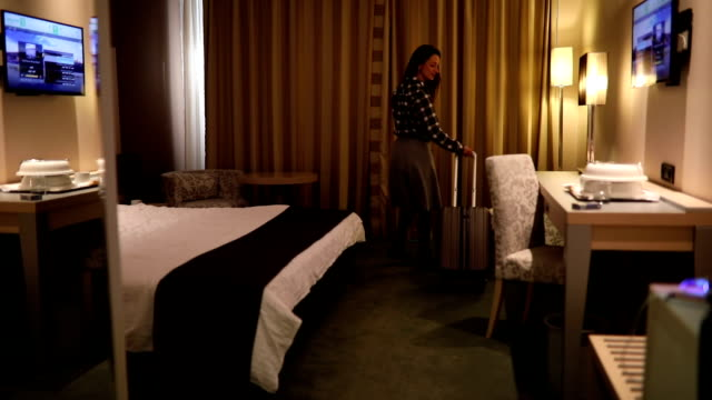 Businesswoman arrives in hotel suite video