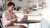 Businesswoman at a table in a cafe using tablet computer video