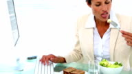 Businesswoman eating lunch at her desk video