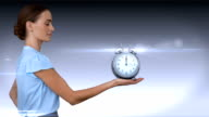 A businesswoman holding alarm clock video