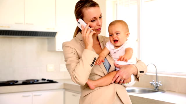 Businesswoman holding baby while talking on the phone video