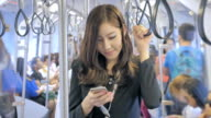Businesswoman holding onto a handle and using smartphone on a train video