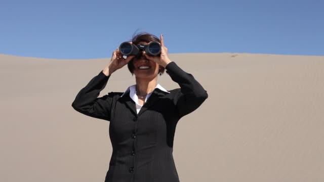 Businesswoman in desert looking through binoculars video
