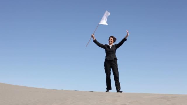 Businesswoman in desert waving white flag video