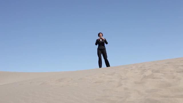 Businesswoman in desert with binoculars video