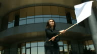 Businesswoman in front of office building waving white flag video