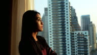 Businesswoman in her office looking out the window. video