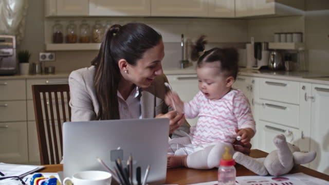 Businesswoman interacting with baby daughter video
