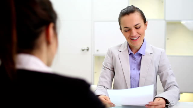 Businesswoman interviewing female candidate video