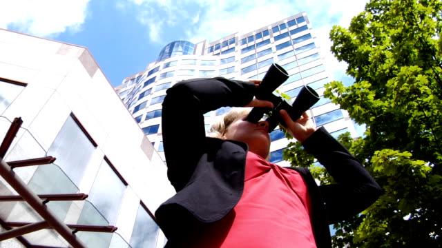 Businesswoman looking through binoculars video
