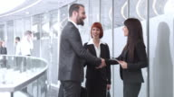 DS Businesswoman meeting with colleagues in corporate hallway video