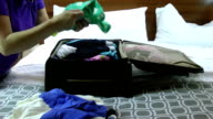 Businesswoman packing in suitcase in hotel room video