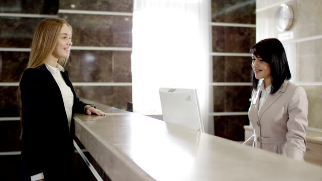 Businesswoman paying for appartment in the hotel at the reception video