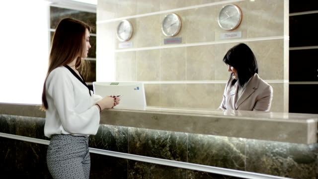 Businesswoman paying for room in the hotel at the reception and get a key video