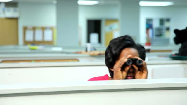 Businesswoman peeks over cubicle with binoculars video