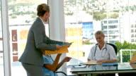 Businesswoman picking medical folder during medical meeting video