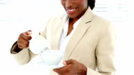 Businesswoman pouring milk into her cup video