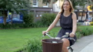Businesswoman Riding Bike Through City Park video