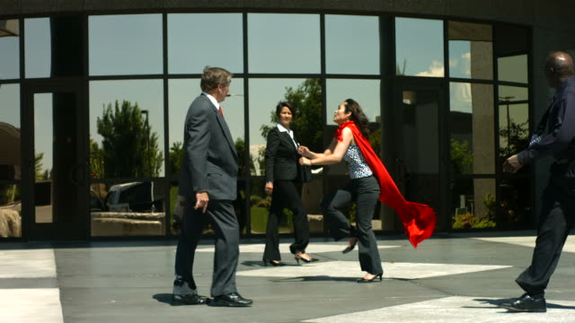 Businesswoman running with superhero cape, slow motion video