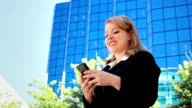 Businesswoman sending text message with cell phone video