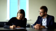 Businesswoman signing contract at interview in office video