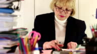 Businesswoman sits at the table in office among commercial papers video