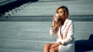 Businesswoman sitting on stairs drinking coffee and thinking. video