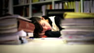 Businesswoman sleeping among stacks of documents video