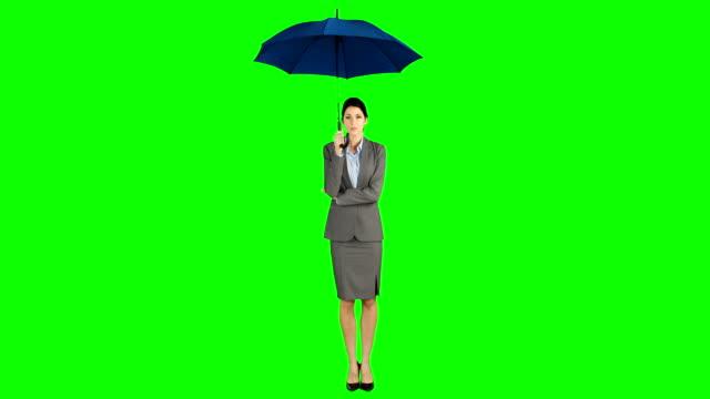 Businesswoman standing under umbrella video
