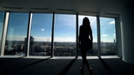 Businesswoman standing with back against office window. video