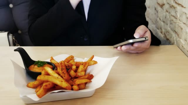 Businesswoman take a break time with french fries and touching smartphone , relaxation concept video