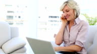 Businesswoman talking on phone and using laptop video