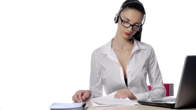 Businesswoman talking on the phone while working on her computer at the office video