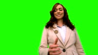 Businesswoman throwing a coin in the air on green screen video