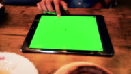 Businesswoman using digital tablet at coffee cafe,Green screen video
